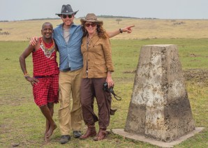 Mike and Nancy pose with safari spotter Sadera at the Tanzania/Kenya border 10 years after their first trip to Africa when he was their spotter back then as well!