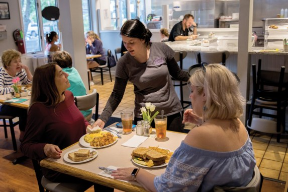 Jen Dollar (center) serves lunch at Evelyn's on September 26, 2018.