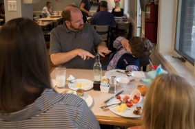 Owner Brandon Stalker takes a moment to eat breakfast with his family.