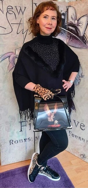 Model wearing black poncho with sparkle diamante detail, polo neck and sleeves.