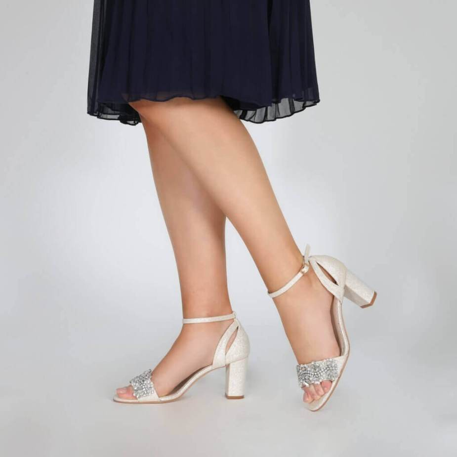 Model wearing Perfect Bridal gold sparkle shoes with block heel and ankle strap