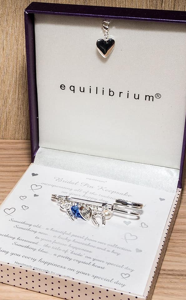 Bridal pin keepsake gift. Comprises of silver pin with 5 charms attached. The charms are a key, a blue crystal heart, a heart with the inscription 'bride', a horseshoe and a pearl