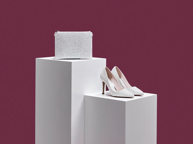 Rainbow Club Coco bridal shoes crafted in ivory snow glitter. Has pointed toes, a contemporary, streamlined shape and stiletto heels. Also pictured is the matching Arizona pouch-style handbag