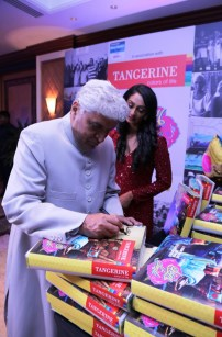 Javed signs for a CSR initative by Tangerine to donate bedsheets to oldage home