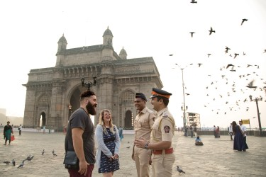 Policemen at Gateway of India interacting with foreign tourists