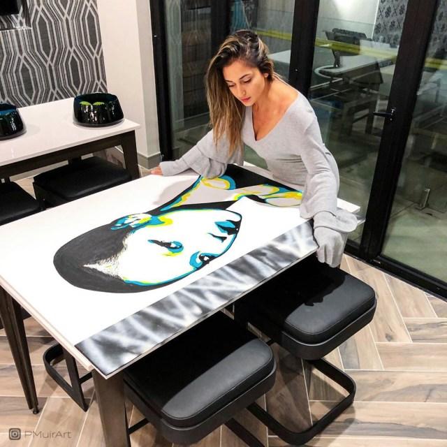 Pratiksha Muir stands with her painting.