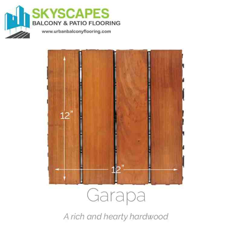 Heavy-duty hardwood four-slat outdoor flooring tile. Face-on view of Garapa wood showing rich, natural wood grain on a slight amber hued deck tile.