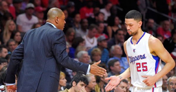 Austin Rivers slaps hands with father Doc during his Clippers debut Friday night in Los Angeles. (AP Photo/Mark J. Terrill)