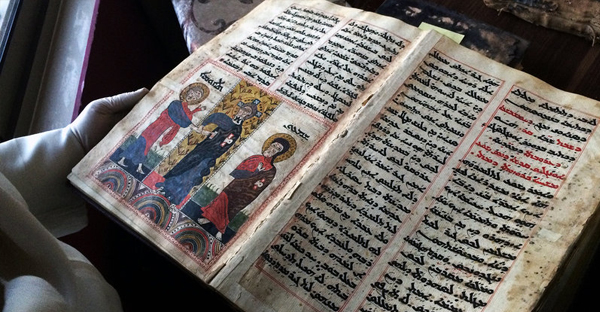 Father Najeeb Michaeel shows off one of the many Christian manuscripts he saved from Iraq's Christian libraries. (Alice Fordham/NPR)