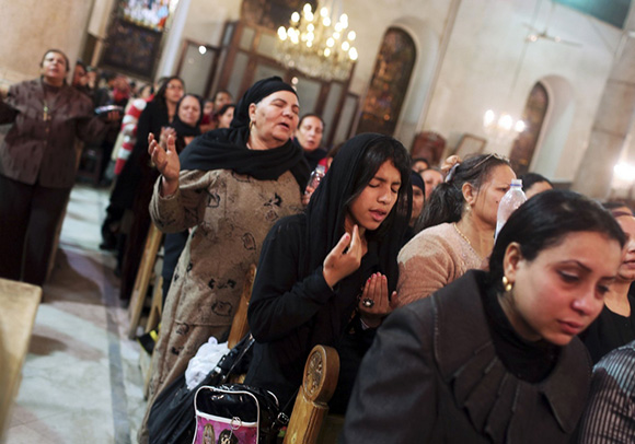 Coptic Orthodox Christian pray during a religious session by father Makary at St Mark Cathedral in Cairo