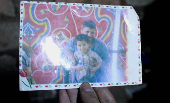 Hani Abdel Messihah, 32, killed by ISIS in Libya, smiles with his young son in a worn photograph.