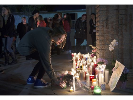 CJ Holton places her candle into a group while people gather out front of El Dorado High School on Monday for a candlelight vigil in remembrance of El Dorado photography teacher Jillian Jacobson. (MATT MASIN)