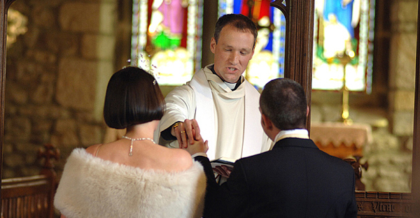 A couple get married with a full wedding ceremony and vicar church. (Paula Solloway/Alamy)