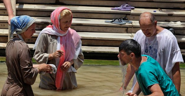 In this July 6, 2015 photo, Christian visitors immerse themselves in the Jordan River at the baptismal area of the Israeli-run site known as Qasr al-Yahud, located in a part of the West Bank, seen from the eastern bank of the river in South Shuna, Jordan. (AP Photo/Raad Adayleh)