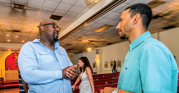 Alton Hardy (l.), pastor of the mostly black Urban Hope Community Church, talks with church member Dion Watts after a Sunday service. (Carmen K. Sisson)