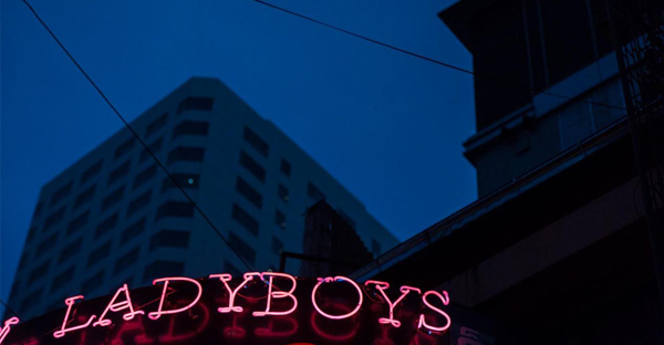 A beacon of red against a dark city skyline, reveals a 'ladyboy' bar in a popular Bangkok red-light district.