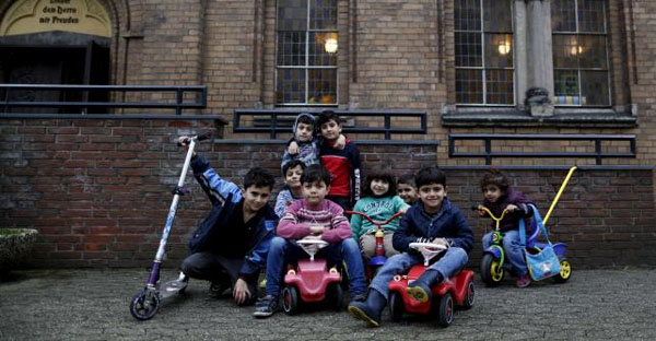 Migrant children from Syria pose in front of a Protestant church in Oberhausen, Germany, November 19, 2015. (REUTERS/INA FASSBENDER)