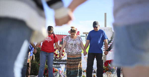 Mourners engage in a group prayer on Dec. 5, 2015 at a makeshift memorial for victims following the shooting attack in San Bernardino, Calif. (Photo courtesy of REUTERS/Sandy Huffaker)
