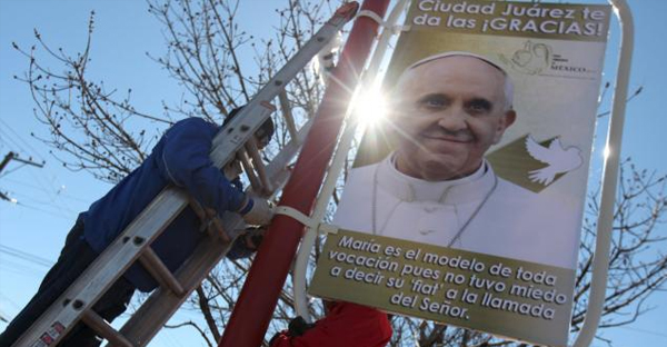 Workers put up a poster with an image of Pope Francis along a street at the border with the U.S. in Ciudad Juarez, Mexico, February 6, 2016. (REUTERS/JOSE LUIS GONZALEZ)