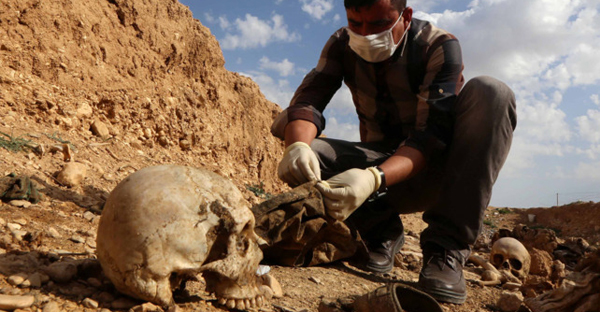 An Iraqi man inspects the remains of members of the Yazidi minority killed by ISIS on February 3, 2015. (Photo: Safin Hamed/AFP/Getty Images)