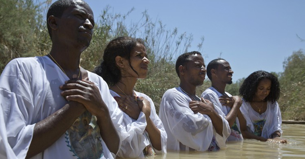 Eritrean Christian migrants now living in Israel pray in the waters of the Jordan River at the Qasr al-Yahud baptism site on May 5. (PHOTO: HEIDI LEVINE FOR THE WALL STREET JOURNAL)