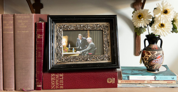 A photo in Mr. Tauton's office shows him with Mr. Hitchens at a debate in St. Louis in 2008. (Credit: Cary Norton for The New York Times)
