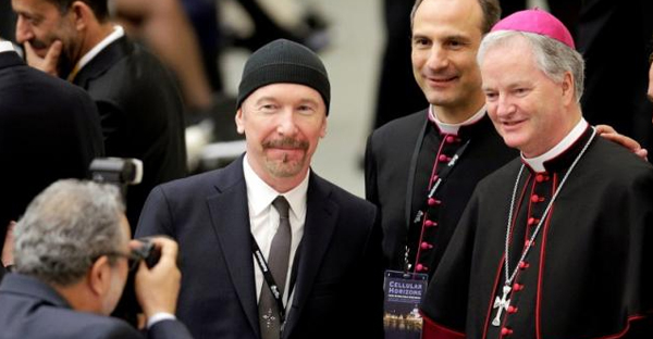 U2 guitarist David Evans, also known by his stage name The Edge, poses with Irish bishop Paul Tighe (R) before listening to U.S. Vice President Joe Biden in Paul VI hall at the Vatican April 29, 2016. (REUTERS/MAX ROSSI/FILE PHOTO)
