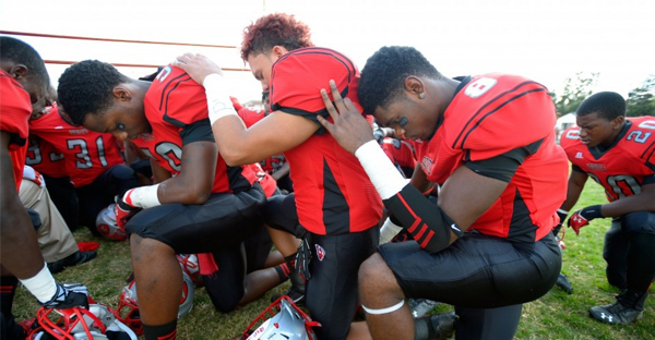 Suitland High School football players, shown here in 2013, pray before and after each game at their Maryland high school. (John McDonnell/The Washington Post)
