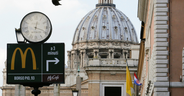 A sign in front of St. Peter's Basilica points to the newest McDonald's restaurant in Rome, next to the Vatican. Jan. 3, 2017. (Photo courtesy of Reuters/Alessandro Bianchi)