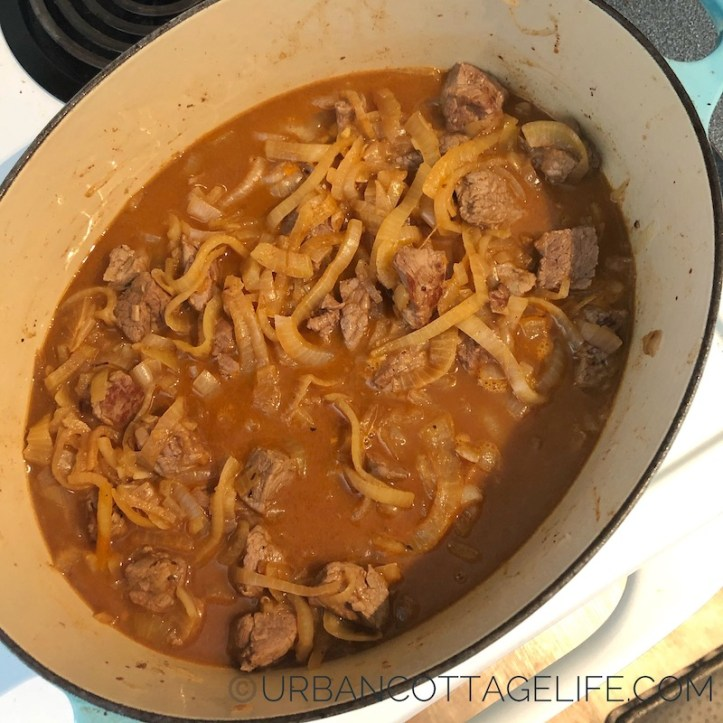 A pot of beef and onions in a parka-hued broth simmers on the stove.