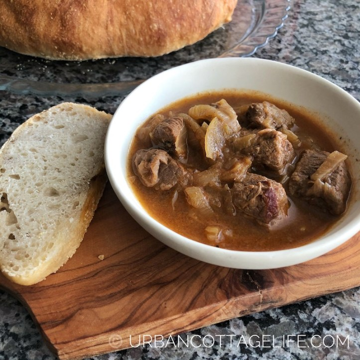 A dish of Hungarian Goulash with a side of crusty bread.