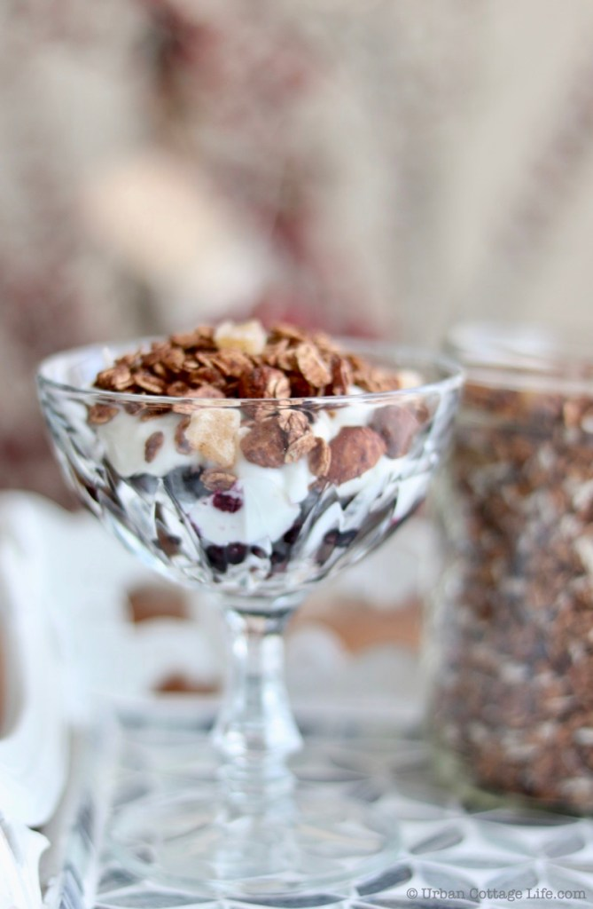 A straight-on shot of a crystal goblet of blueberries topped with plain yogourt and then chocolate ginger granola, with a jar of granola blurred out in the background.