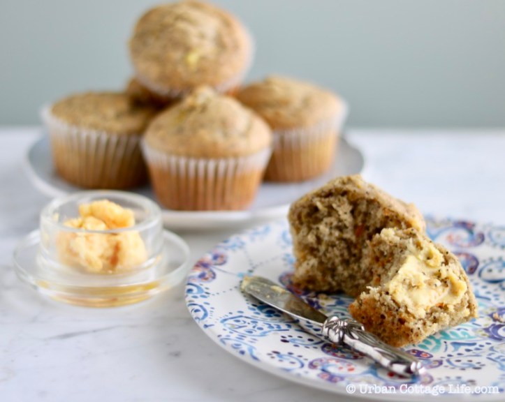 A partially eaten muffin with orange maple butter on it, with a glass dish of the compound butter beside it and a platter of muffins in the background.