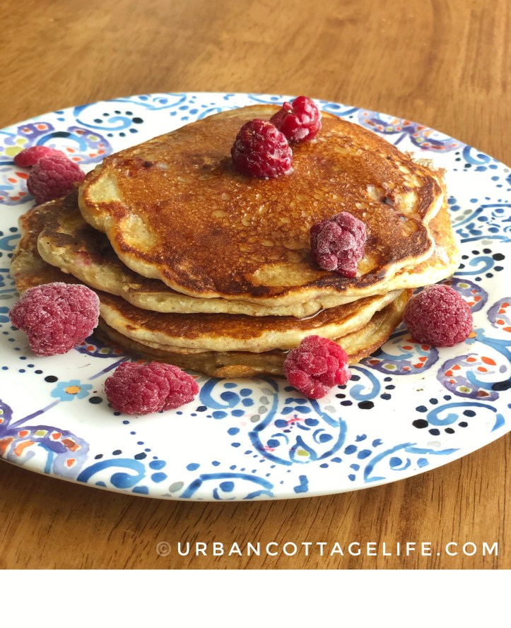 A colourful plate holds a stack of maple syrup-kissed cornmeal raspberry pancakes garnished with raspberries