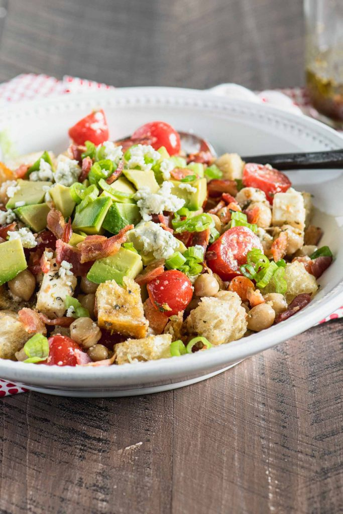 Close up of panzanella salad with tomatoes, green onions, bread cubes and bacon