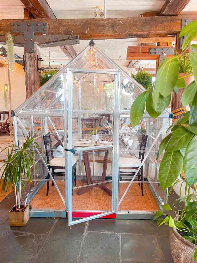 Dine in a fancy looking greenhouse at Au Jardin