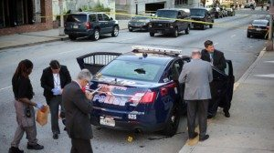 Atlanta Police investigate the scene of a shooting Thursday, April 30, 2015, in Atlanta. Police say officers fatally shot a woman who first fired at them while sitting in the back of a patrol car in Atlanta. (Ben Gray/Atlanta Journal-Constitution via AP)