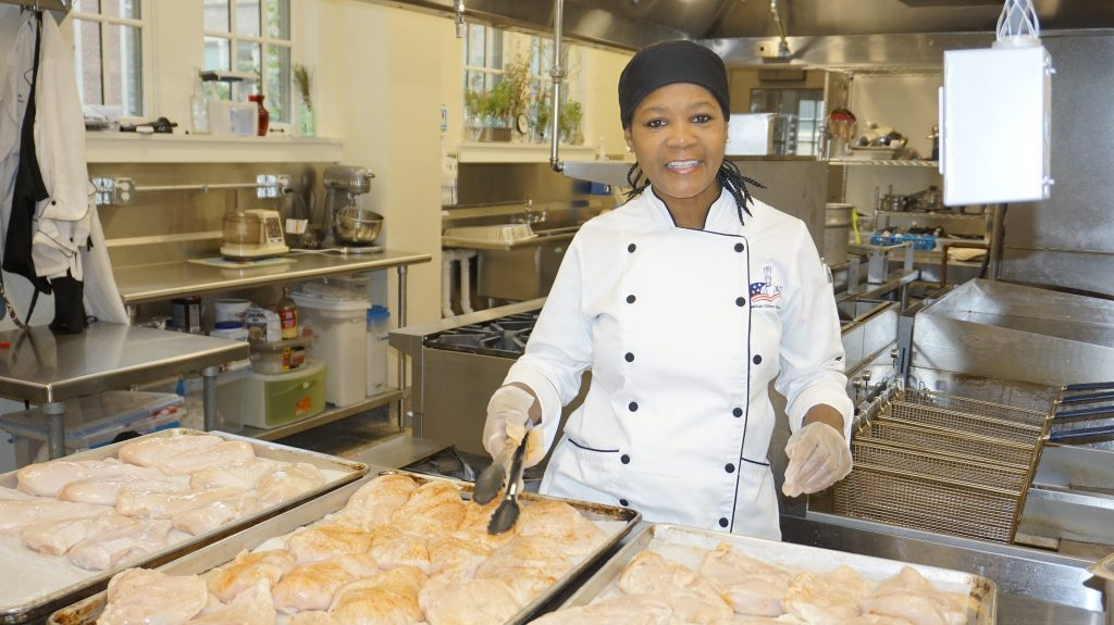Lisa McKay, in her kitchen in the Wgemas Building, seasons chicken in preparation for a recent catering job. Photo by Andrea Waxman/NNS.