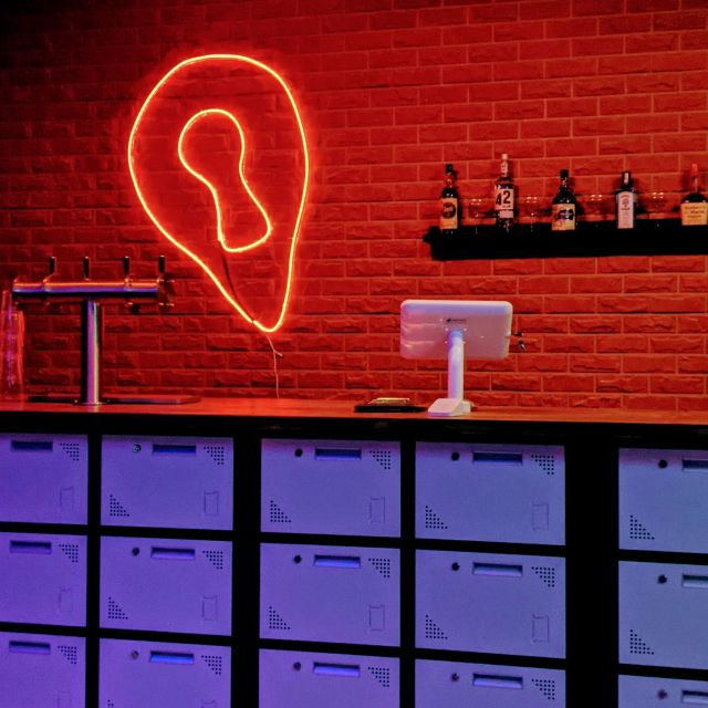 A neon sign shaped like a keyhole on a brick wall in the Mystery Bar