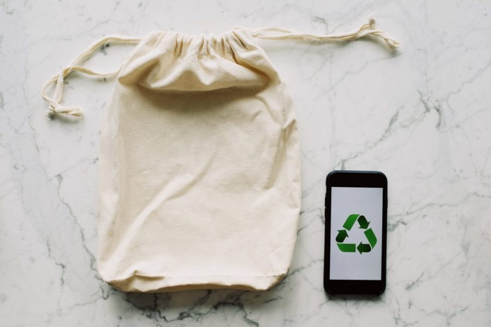 white textile bag and smartphone with recycle logo
