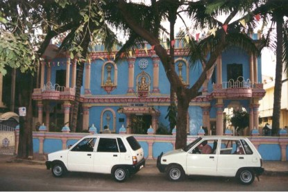 Sathya Sai Baba center building with trees and two small cars in front