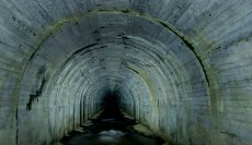 Looking down the long tunnel to the black abyss at the end.
