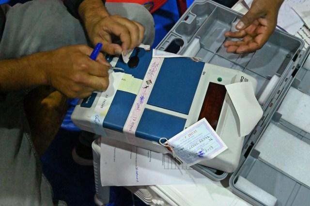 سیل الیکٹرانک ووٹنگ مشین کو کھولا جارہا ہے۔