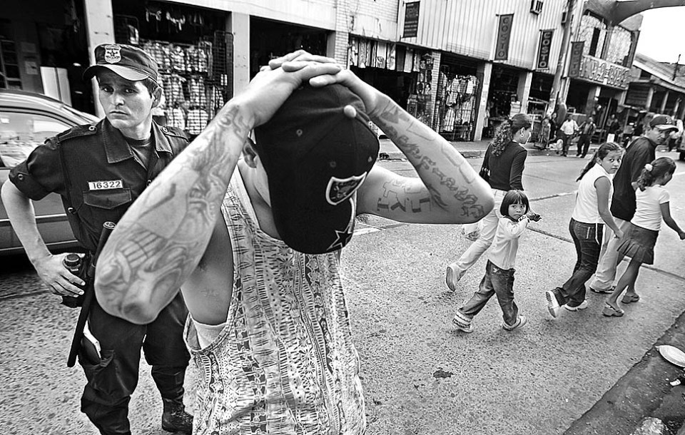 "July 8, 2005 -- Passersby in Santa Tecla, El Salvador, look on as a police officer detains a member of the Mara Salvatrucha street gang as part of an ongoing operation called ""Mano Dura,"" which means ""hard hand."""