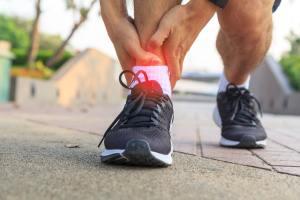 Man holding injured ankle