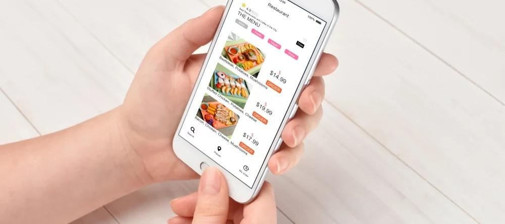 Food Apps und Vitamin B12. Das Foto zeigt ein Mädchen, das an einem Tisch sitzt und mit Hilfe einer App etwas zu Essen bestellt.