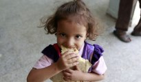 A displaced Yemeni child, who fled the Saada province with her family, eats bread at a school turned into a shelter in the capital Sanaa on Wednesday.