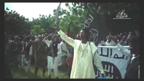 """A screenshot from a video purportedly released by Boko Haram on September 13 shows a speaker for the group raising a sword amid a crowd of followers in an undisclosed location. The speaker said the group will """"capture"""" Nigeria's President Muhammadu Buhari."""