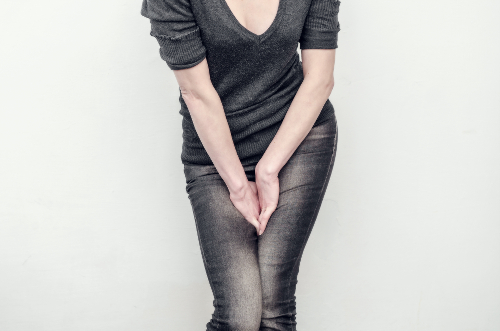 woman holding her bladder due to leakage