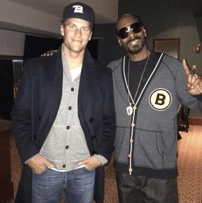Snopp Dogg poses with Tom Brady while rocking a throwback Boston Bruins sweatshirt.